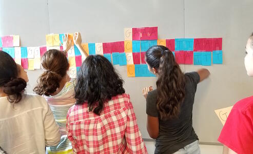 Middle school girls using post-it notes as a hands-on approach in learning about DNA and it's structure.
