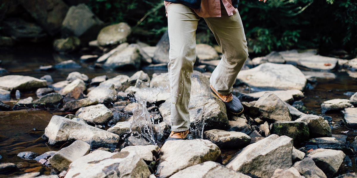 Man walking on rocks in the middle of a stream collecting eDNA samples to use with a water filter.